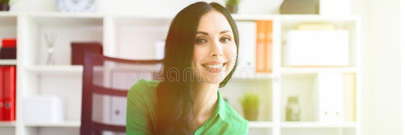 Una ragazza si siede alla tavola dell'ufficio e tiene una matita in sue mani fotografia stock libera da diritti