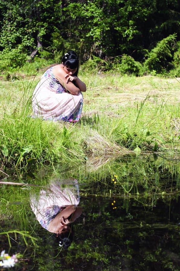 Una ragazza si siede dall'acqua fotografie stock libere da diritti