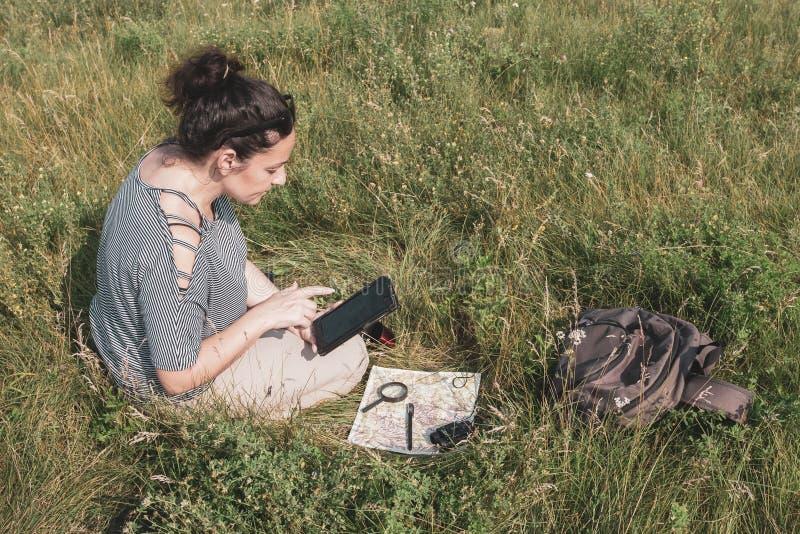 Una ragazza si siede nell'erba e fa un itinerario facendo uso di una compressa e di una mappa immagini stock libere da diritti