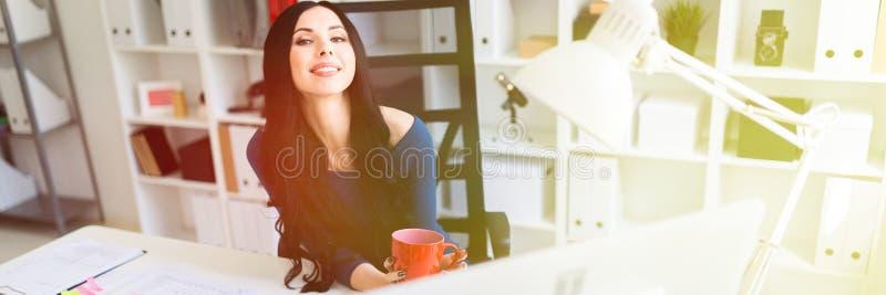 Una ragazza si siede nell'ufficio alla tavola e tiene una tazza rossa in sue mani fotografia stock libera da diritti