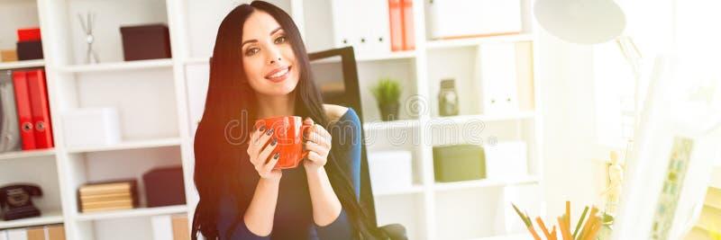 Una ragazza si siede nell'ufficio alla tavola e tiene una tazza rossa in sue mani immagini stock libere da diritti