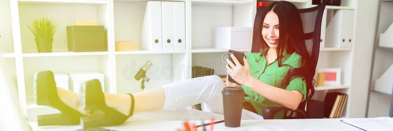 Una ragazza si siede nell'ufficio, ha gettato le sue gambe sulla tavola e tiene il telefono in sue mani fotografie stock