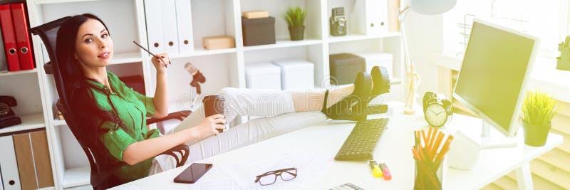 Una ragazza si siede nell'ufficio, ha gettato le sue gambe sulla tavola e tiene un vetro di caffè fotografia stock