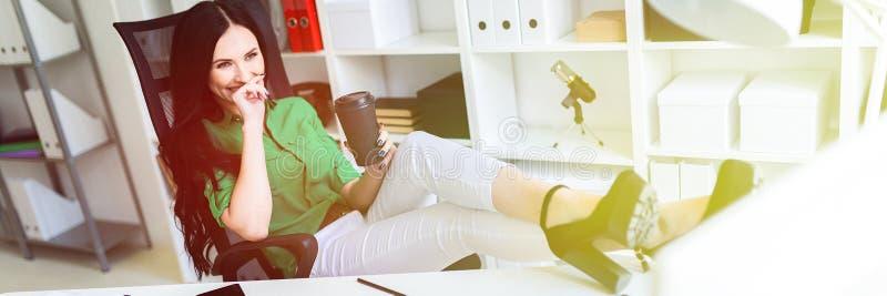 Una ragazza si siede nell'ufficio, ha gettato le sue gambe sulla tavola e tiene un vetro di caffè immagine stock libera da diritti