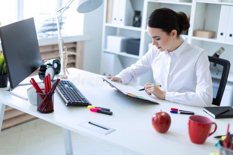 Una ragazza si siede nell'ufficio, tiene una penna in sua mano e guarda attraverso i documenti fotografia stock