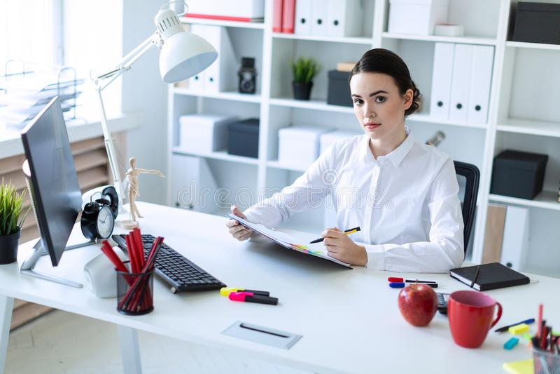 Una ragazza si siede nell'ufficio, tiene una penna in sua mano e guarda attraverso i documenti immagine stock libera da diritti