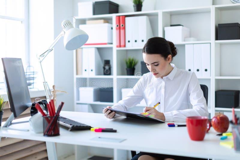 Una ragazza si siede nell'ufficio, tiene una penna in sua mano e guarda attraverso i documenti immagine stock