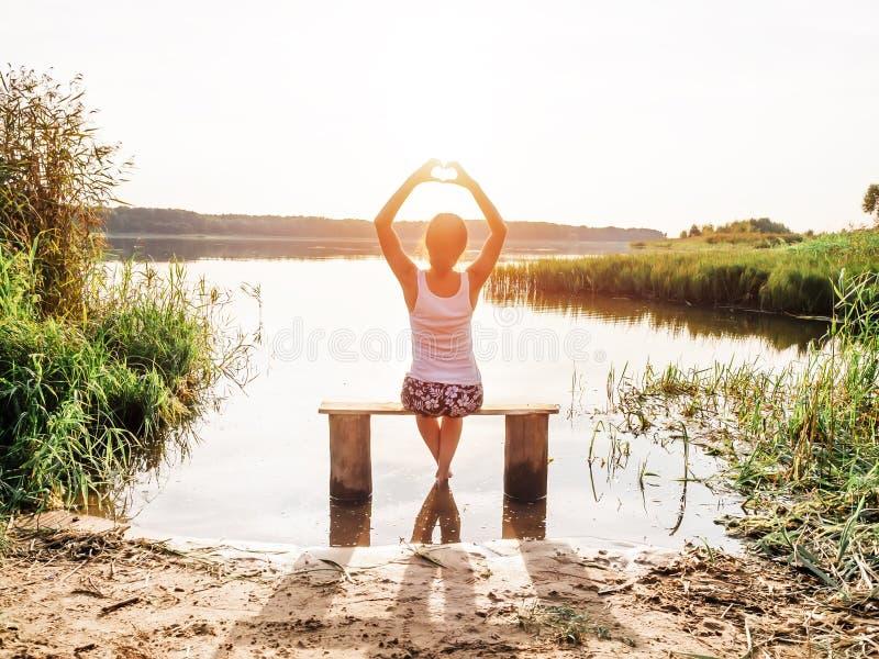 Una ragazza si siede su un banco dal fiume gode di bello tramonto e mostra il segno del cuore delle dita delle mani Ragazza nella fotografia stock