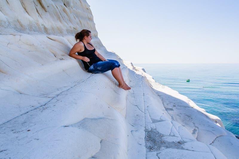 Una ragazza si siede su un pendio della scogliera bianca chiamato & di x22; Dei Turchi& x22 di Scala; in Sicilia immagini stock libere da diritti