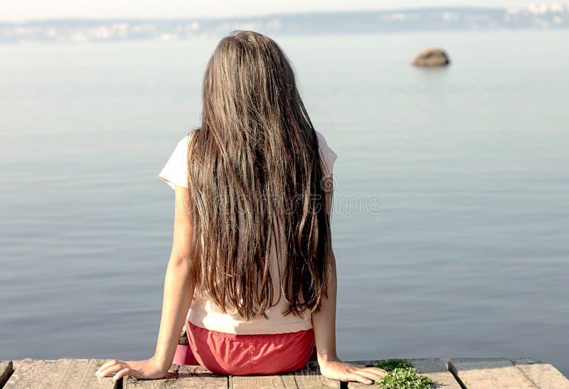 Una ragazza si siede sull'orlo di un pilastro vicino all'acqua e esamina la distanza immagine stock libera da diritti