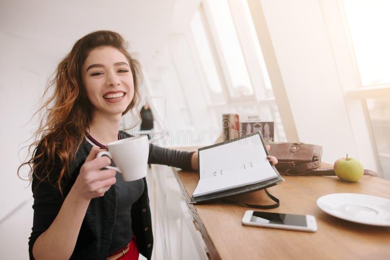 Una ragazza si siede in un caffè, tenente una tazza di caffè in una mano ed in altro taccuino immagini stock libere da diritti