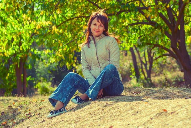 Una ragazza si siede in uno schiarimento nel legno immagine stock