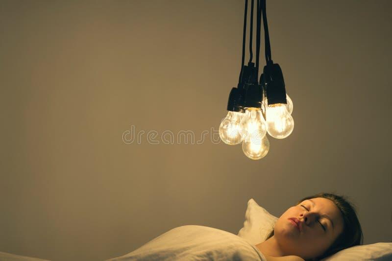 Una ragazza si trova a letto sotto le grandi lampadine inscatola il ` t per cadere addormentato Immagine di concetto insonnia psi fotografie stock