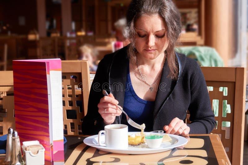 Una ragazza sola ha prima colazione nel ristorante con i dolci ed il tè immagini stock libere da diritti