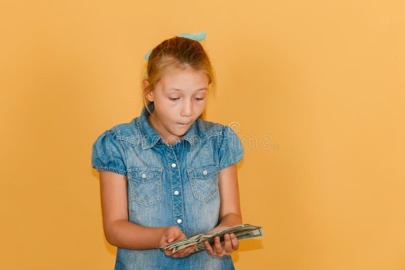 Una ragazza sorpresa e gioiosa guarda con ammirazione i dollari che vive nelle sue mani immagini stock