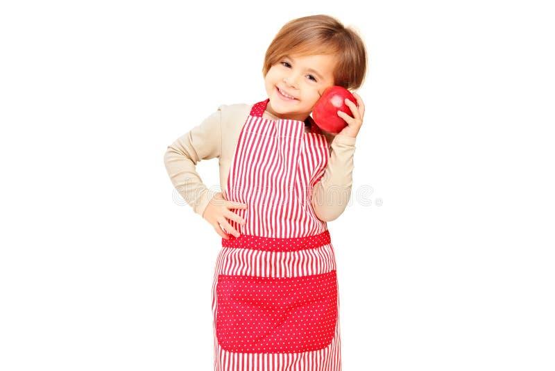 Una ragazza sorridente con il grembiule che tiene una mela rossa immagini stock