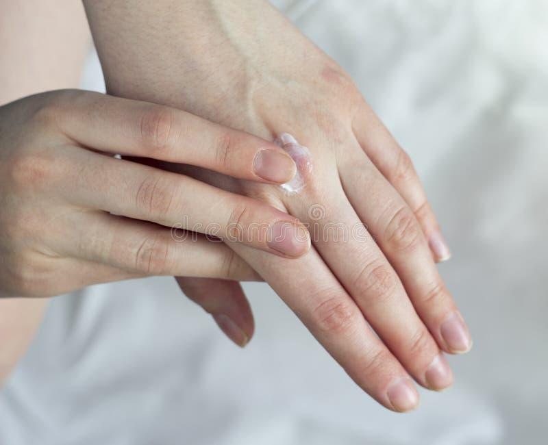 Una ragazza spalma una crema per le mani su una crema bianca del fondo immagini stock libere da diritti
