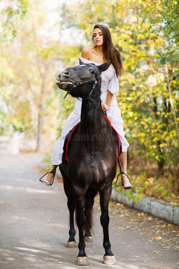 Una ragazza sta guidando su un cavallo nero che la esamina all'esterno fotografie stock