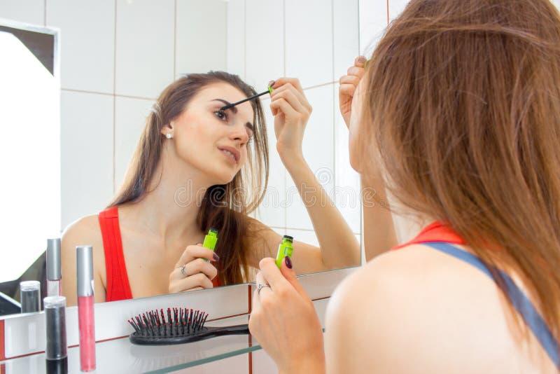 Una ragazza sta nel bagno attraverso dagli specchi e le pitture osserva fotografia stock libera da diritti