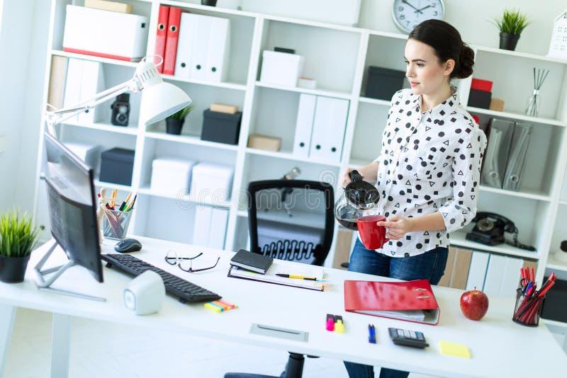 Una ragazza sta nell'ufficio vicino alla tavola e versa il caffè dalla caffettiera in una tazza rossa fotografie stock libere da diritti