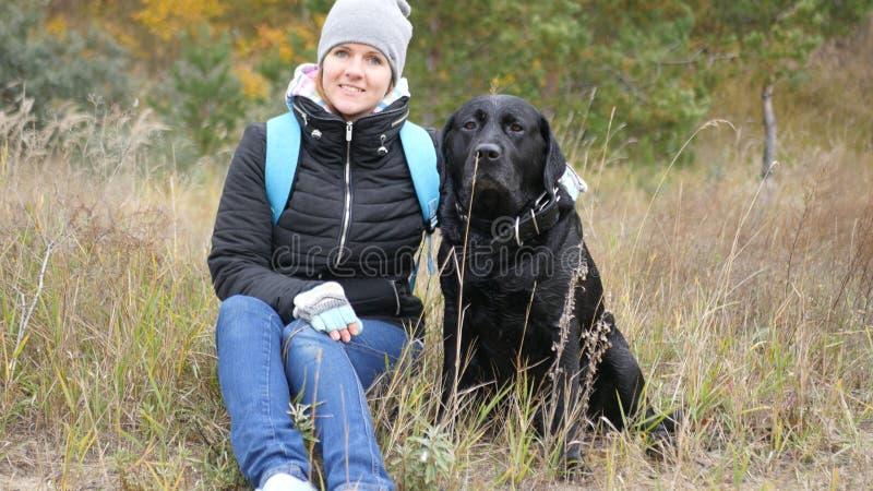 Una ragazza sta prendendo le immagini con il suo cane, esaminante la macchina fotografica foto immagine stock