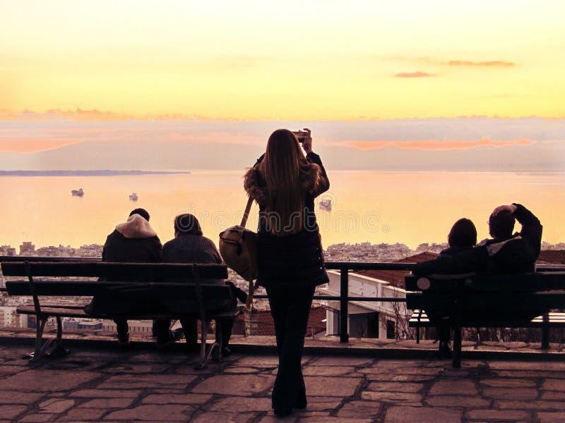 Una ragazza sta prendendo le immagini di un tramonto alla piattaforma di osservazione fotografie stock libere da diritti