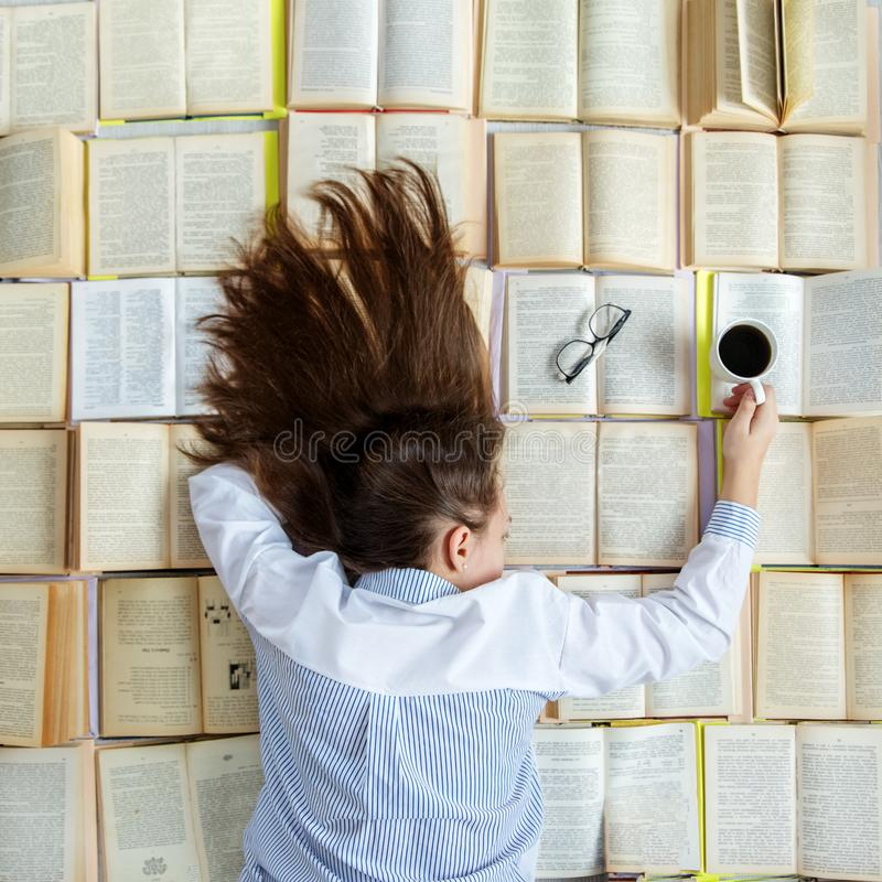 Una ragazza sta preparando per gli esami Molti libri Concetto per il giorno del libro del mondo, stile di vita, studio, istruzion fotografie stock