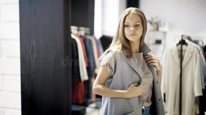 Una ragazza sta provando su un rivestimento grigio in un negozio fotografia stock