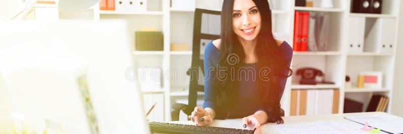 Una ragazza sta sedendosi all'ufficio alla tavola ed al testo di battitura a macchina sulla tastiera immagine stock