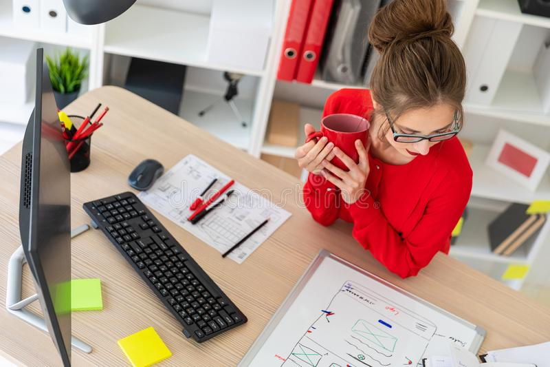 Una ragazza sta sedendosi alla tavola nell'ufficio, sta tenendo una tazza di caffè e sta esaminando il bordo magnetico immagini stock