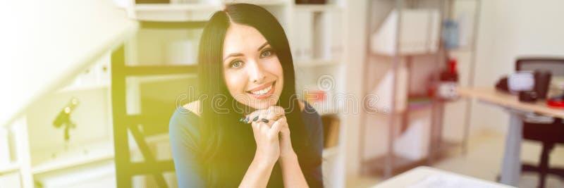 Una ragazza sta sedendosi nell'ufficio alla tavola fotografia stock libera da diritti
