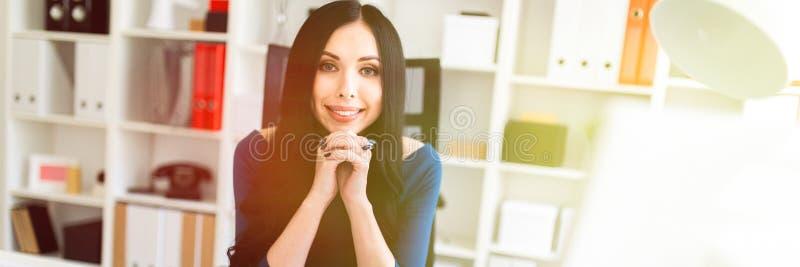 Una ragazza sta sedendosi nell'ufficio alla tavola fotografia stock