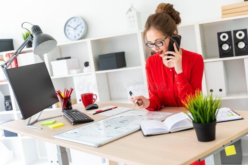 Una ragazza sta stando ad una tavola nell'ufficio, sta tenendo un indicatore nero in sua mano e sta parlando sul telefono La raga fotografie stock