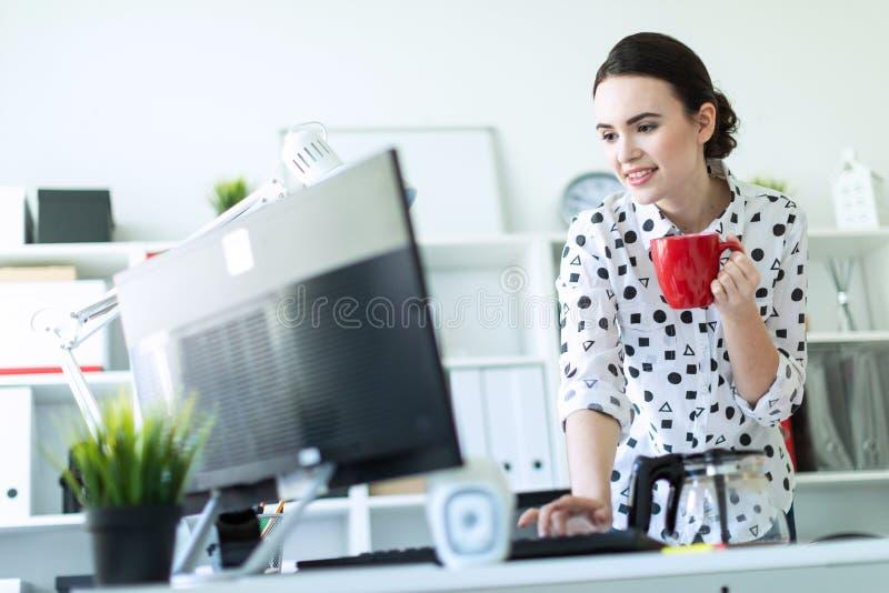 Una ragazza sta stando nell'ufficio vicino alla tavola, sta tenendo una tazza rossa in sua mano e sta scrivendo sulla tastiera fotografia stock