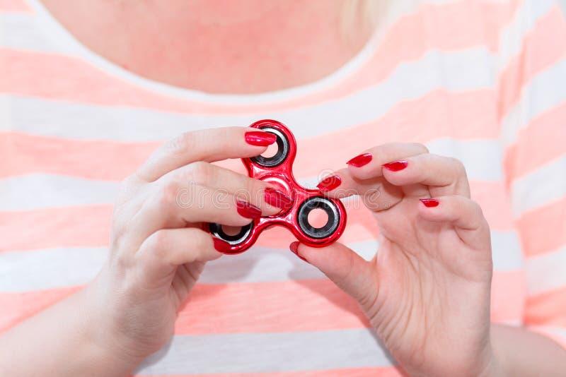 Una ragazza sta tenendo un filatore popolare di irrequietezza del giocattolo in sue mani Streptococco fotografie stock libere da diritti