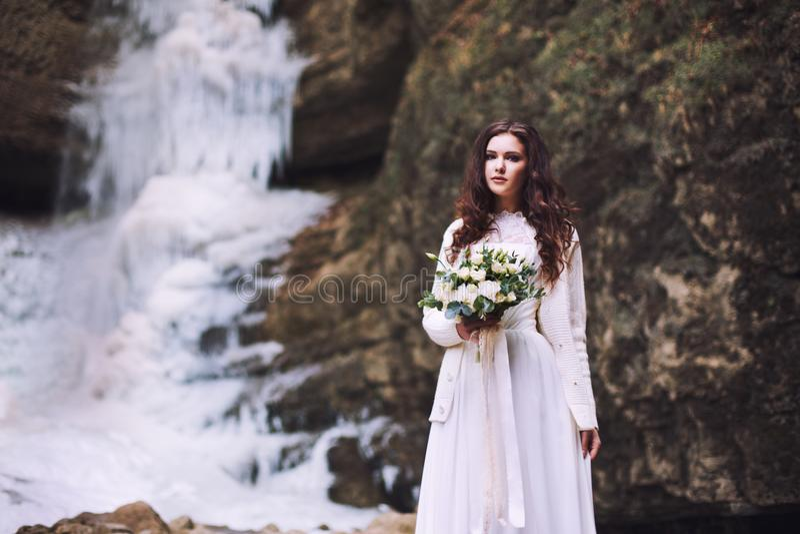 Una ragazza sta tenendo un mazzo di nozze dei fiori contro lo sfondo di un ghiacciaio e delle montagne fotografia stock libera da diritti