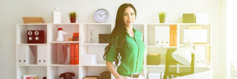 Una ragazza sta vicino ad una scrivania fotografia stock