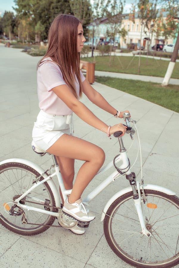 Una ragazza su una bicicletta, di estate nella città, una passeggiata nell'aria fresca, uno stile di vita attivo di sport della g fotografie stock libere da diritti