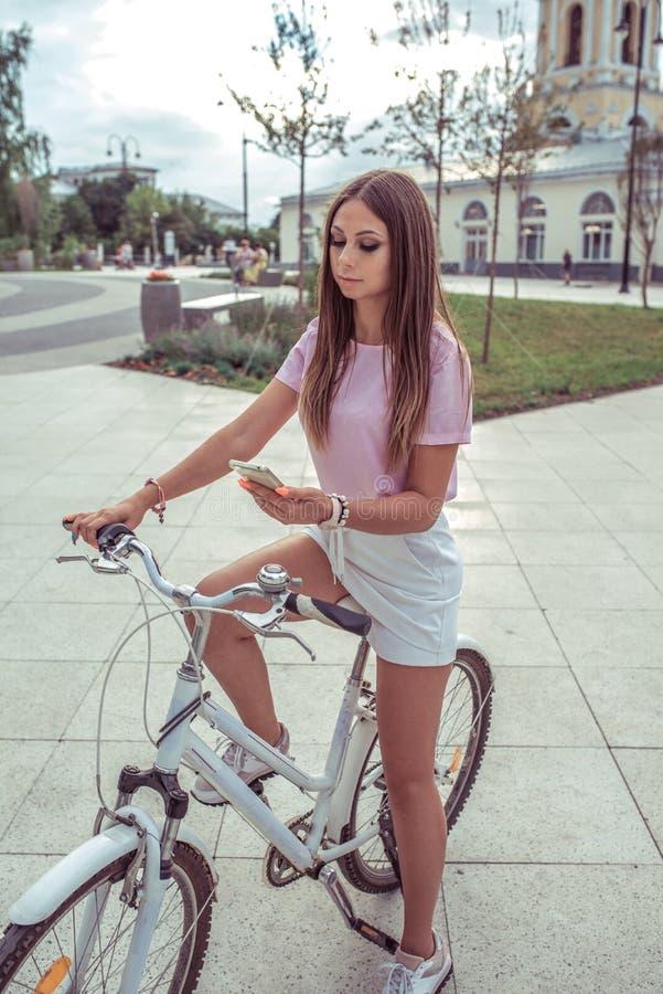 Una ragazza su una bicicletta, di estate nella città, in sua mano uno smartphone, navigatore, esamina l'itinerario, modulo di isc fotografie stock