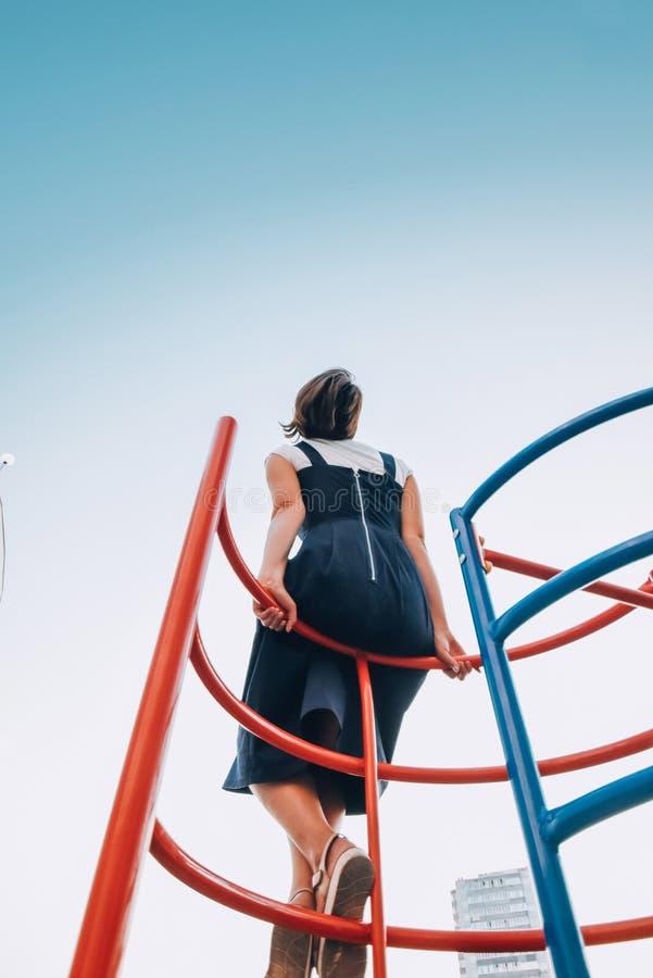 Una ragazza sulla scala di un bambino esamina un chiaro cielo blu Concetto del sogno dell'infanzia fotografia stock