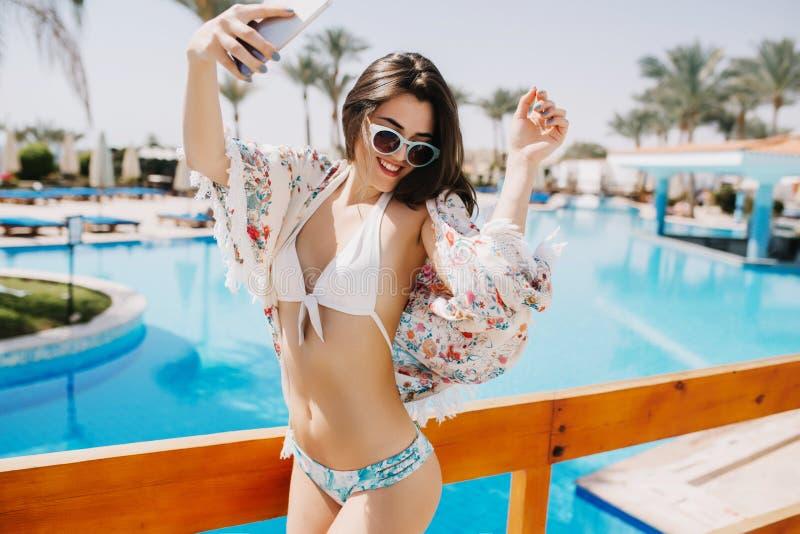 Una ragazza suntanned esile con ballare divertente dei capelli marroni brillanti dallo stagno e la risata sul paesaggio del sud G fotografia stock