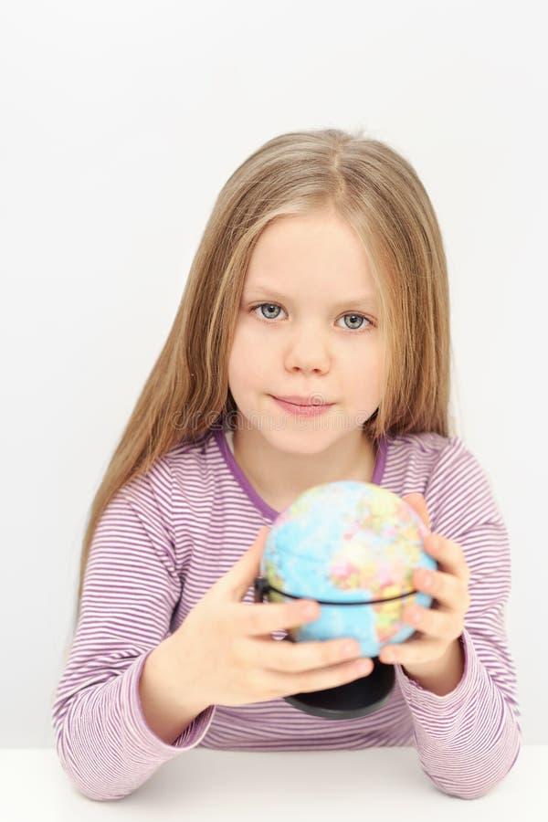 Una ragazza sveglia con il globo sta sognando dei viaggi fotografie stock libere da diritti