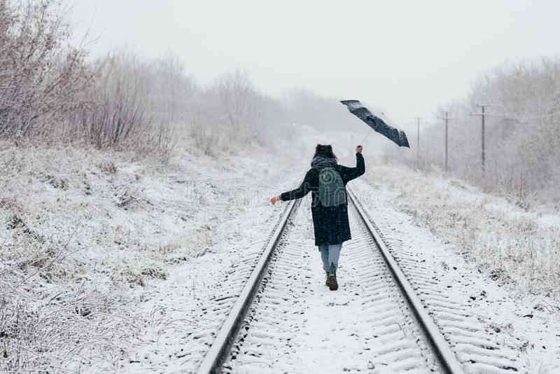 Una ragazza sveglia tiene l'ombrello nelle mani della stagione invernale immagini stock