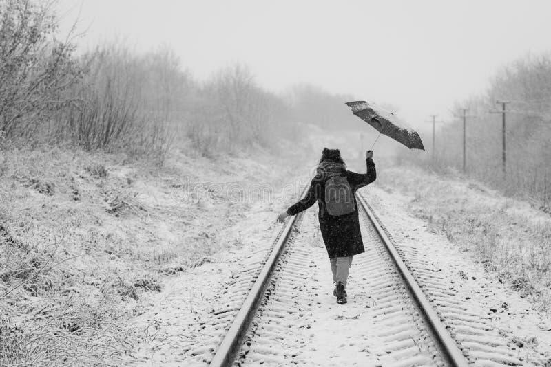 Una ragazza sveglia tiene l'ombrello nelle mani della stagione invernale immagini stock libere da diritti