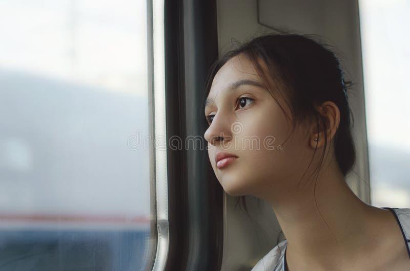 Una ragazza sveglia viaggia in treno e guarda fuori la finestra fotografia stock libera da diritti