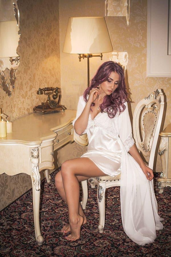 Una ragazza tenera intelligente sta sedendosi in una vestaglia di seta immagine stock