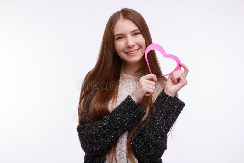 Una ragazza, tenute un cuore rosa e sorrisi Isolato su priorità bassa bianca fotografie stock libere da diritti