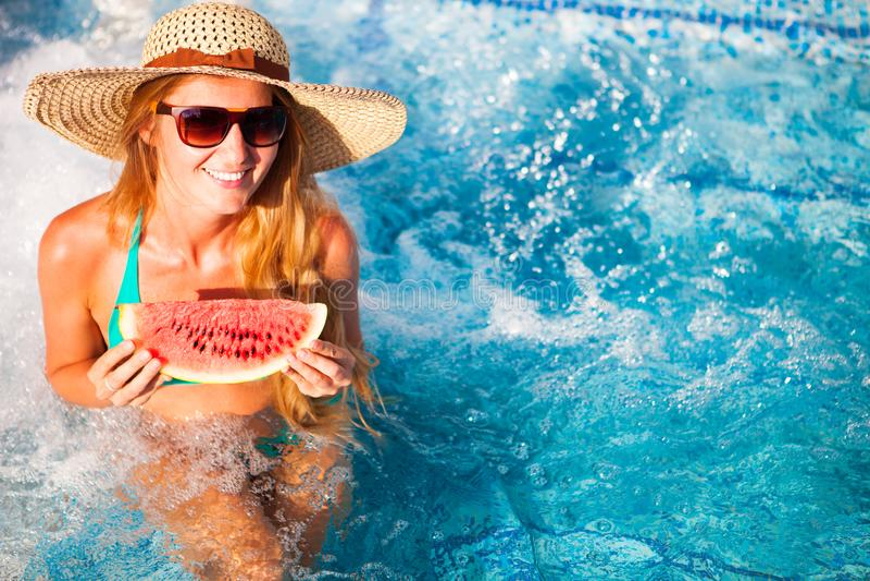 Una ragazza tiene l'anguria rossa mezza sopra uno stagno blu, rilassantesi la o immagini stock libere da diritti