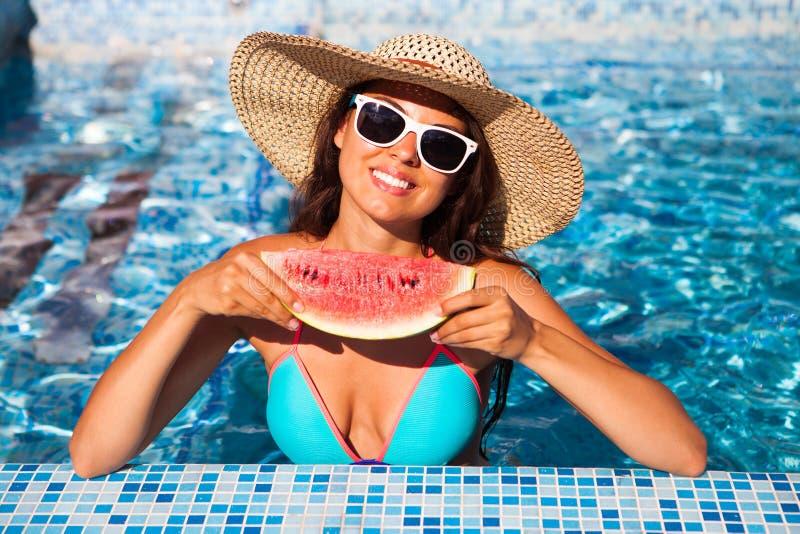 Una ragazza tiene l'anguria rossa mezza sopra uno stagno blu, rilassantesi la o immagine stock libera da diritti