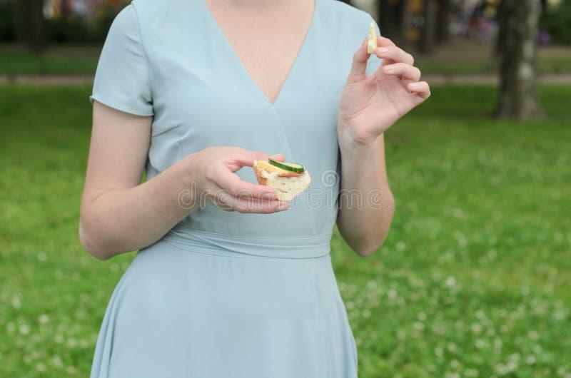 Una ragazza tiene un panino con il prosciutto, il formaggio e una fetta di cetriolo in sua mano ad un picnic nel parco Estate san fotografie stock